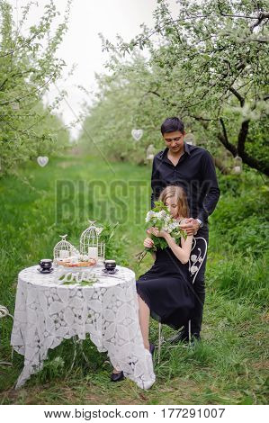 Wonderful love story in photos. Pretty pair in green fruit garden trinking tea in a booth