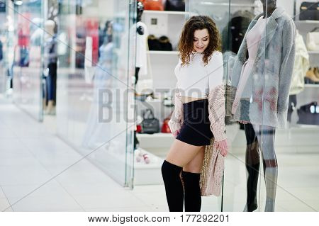 Young Curly Model Girl Posed On Mini Skirt At Large Shopping Center Near Showcase With Mannequin.