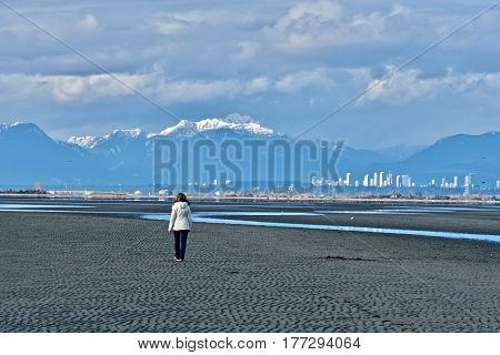 Woman walking on beach with downtown Vancouver and mountains view. Boundary Bay Regional Park in Tsawwassen. Great Vancouver. British Columbia, Canada.