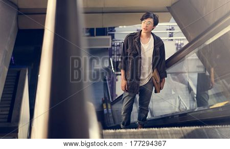 Asian man on escalator going up