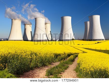 Panoramic view of Nuclear power plant Jaslovske Bohunice with golden flowering field of rapeseed canola or colza - Slovakia - two possibility for production of electric energy