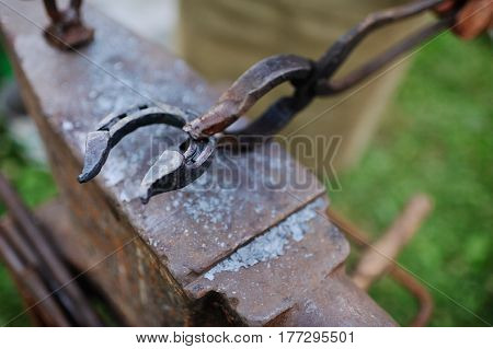 The smith makes a horseshoe on the anvil close-up