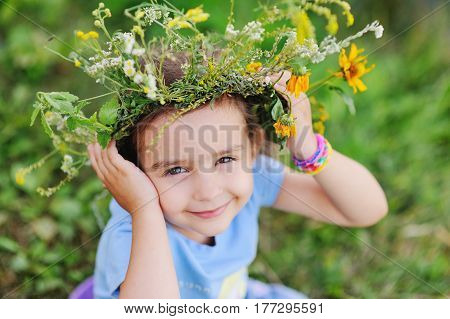 Baby girl in wreath of wild flowers and background of nature. Midsummer day. Easter. Ivan Kupala