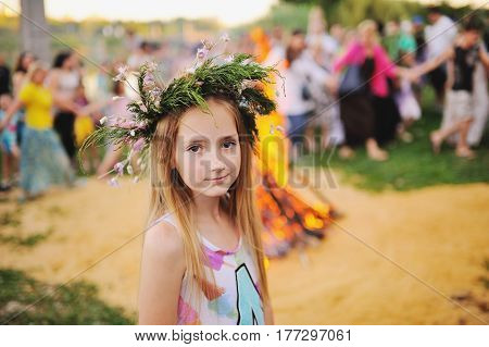 Girl with a wreath of wild flowers on her head against the backdrop of a large fire. Celebrating the pagan holiday of the Slavs - Ivan Kupala