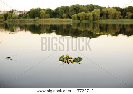 Wreaths of wild flowers float on the river against the backdrop of sunset and nature