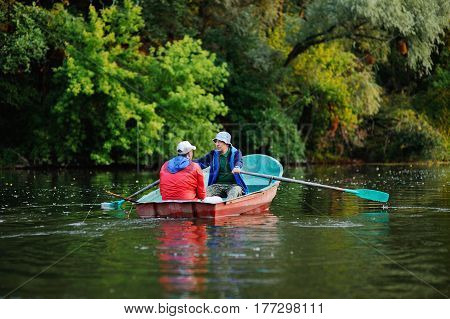 Two fishermen in a red boat with oars with fishing rods catching fish on the background of the river and nature