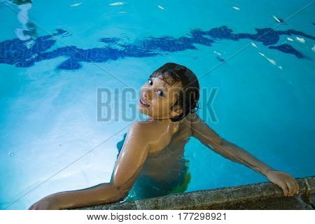 Young boy in a swimming pool handing on the ledge.