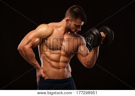 Handsome power athletic man with dumbbell confidently looking forward. Strong bodybuilder with six pack, perfect abs, shoulders, biceps, triceps and chest isolated on black background with copyspace.