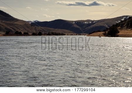 Landscape of Madison river in Montana with mountains and clouds.