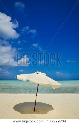 umbrella on idyllic tropical sand beach.White beach umbrella and blue sky.Sun and umbrella on the beach.Summer beach landscape .