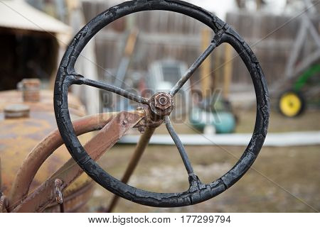 Old Tractor Steering Wheel with other farm equipment in background.