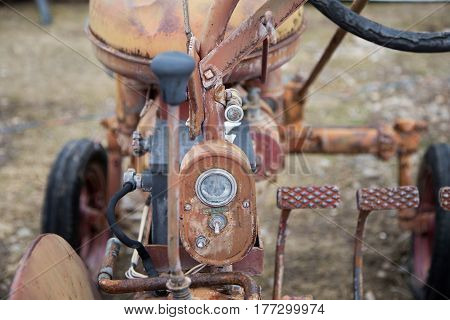 Old vintage rustic tractor that is broken down.