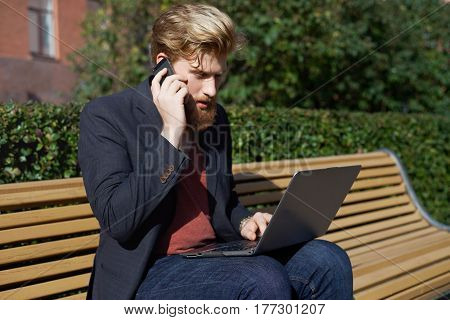 Beard business man have negotiate outdoor Stock manager in work anytime and everywhere Trendy dressed trader outdoor in sunny weather with phone and notebook Male try increase income in the internet.