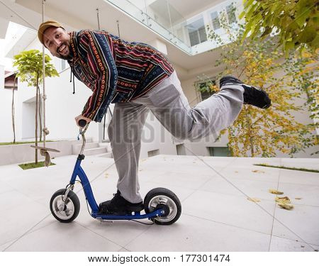 Happy playful adult man on scooter in front of his modern house