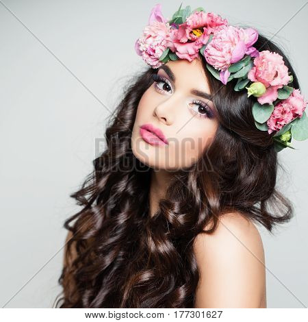 Beauty Face. Cute Woman with Curly and Flowers on Background