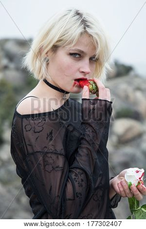 Beautiful young Russian girl with blond hair and blue eyes eating a strawberry in the field. She is dressed in a transparent black dress.