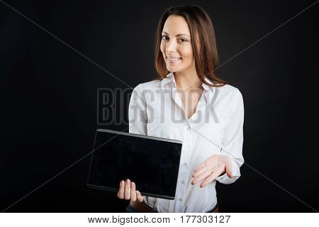 It helps in work. Delighted female keeping smile on her face holding device in right hand while standing over black background