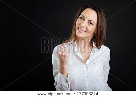 Time to win. Positive delighted woman wearing white shirt keeping smile on her face while standing over black background