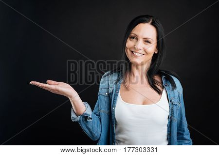 Good mood. Positive delighted black-haired woman wearing casual clothes keeping smile on her face while posing on camera