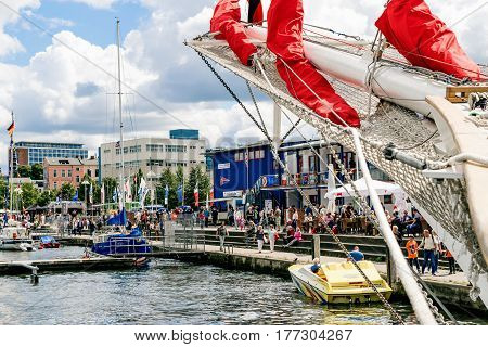 Rostock, Germany - August 2016: Details of bowsprit and gathered red sail of the tall ship on the cloudy sky background. Hanse Sail.