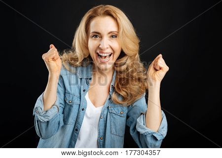 Have fun. Delighted female with curly hair keeping smile on face making fists while looking straight on camera, isolated on black