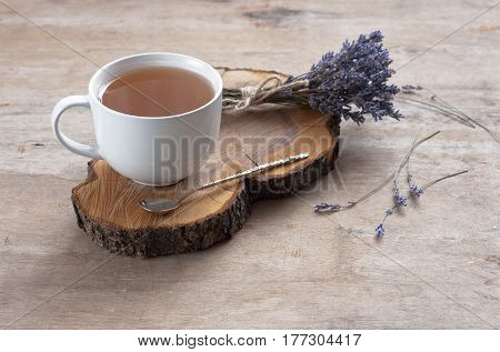 A cup of hot tea and lavender on a wooden background. Herbal tea Hot drink Lavender Mood Breakfast Morning