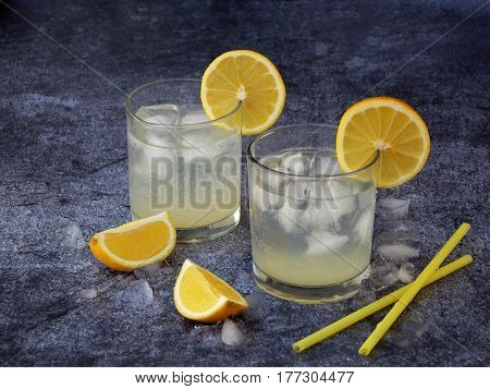 Two Glasses Of Cold Homemade Lemonade With Lemon Slices, Ice Cubes And Straws On Dark Background. Co