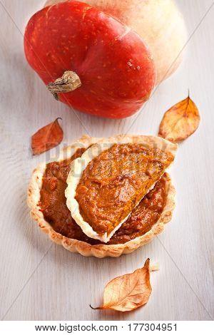 Pumpkin and Pumpkin pie dessert on a wooden surface