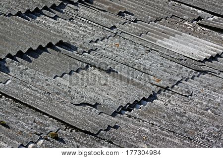Old destroyed asbestos roof. Asbestos roofing design.