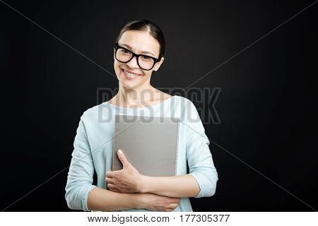 Ready for studying. Good looking female wearing glasses keeping smile on face while embracing her big grey folder