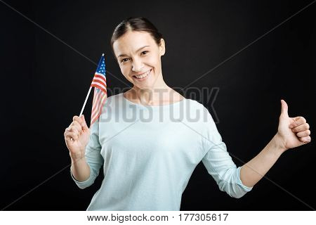 Try to emigrate. Smiling young woman keeping her left thumb up holding little flag in right hand while looking friendly on camera