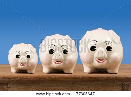 Three piggybanks in small, medium and large sizes sitting on a wooden shelf or table waiting for savings