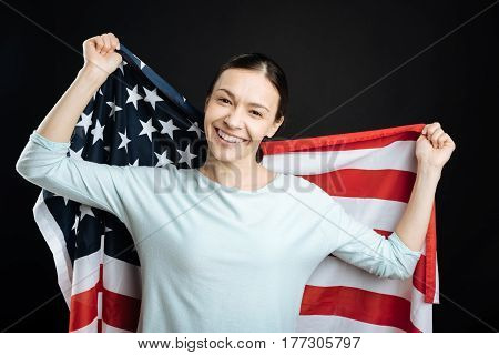 In preparation. Happy brunette wearing blue jumper posing over American flag looking straight on camera