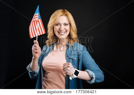 Be inspired. Attractive smiling female wearing smart watches making fist, holding flag in right hand