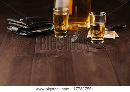 Money And Whiskey On Wooden Table. Close-up View