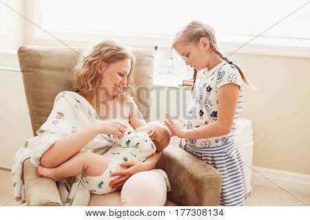 Group portrait of white Caucasian family of three mother breastfeeding newborn baby older sibling sister girl standing watching touching lifestyle candid real life emotions