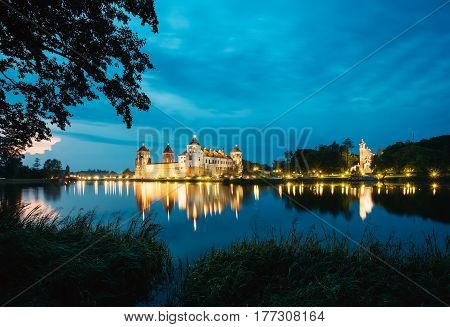 Mir, Belarus. Mir Castle Complex In Bright Evening Illumination With Glow Reflexions On Lake Water. Famous Landmark, Ancient Gothic Monument Of Feudalism Under Blue Dramatic Sky.