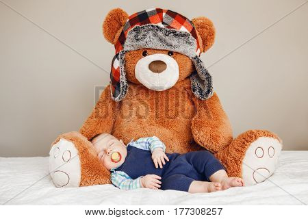 Portrait of a cute adorable white Caucasian baby newborn boy sleeping dreaming with pacifier soother in mouth wearing shirt blue onesie lying on bed with large soft bear toy