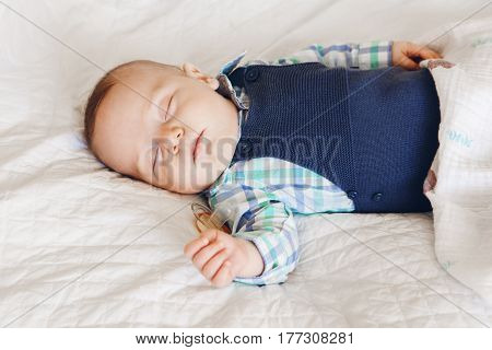 Portrait of a cute adorable white Caucasian baby newborn boy girl sleeping dreaming with pacifier soother in mouth wearing shirt onesie lying on bed covered with blue blanket