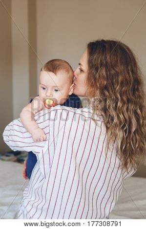 Portrait of middle age young Caucasian mother with long wavy blonde hair in white striped shirt holding newborn baby son daughter on shoulder kissing him in cheek