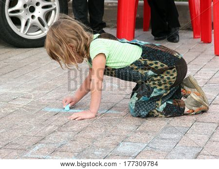 Small painter paints a blue chalk on a cobblestone pavement
