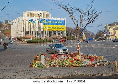 KIEV, UKRAINE - MARCH 22, 2014: Flowers for the dead ahead The International Convention Center with large revolution banner - The uniform country of United Country.