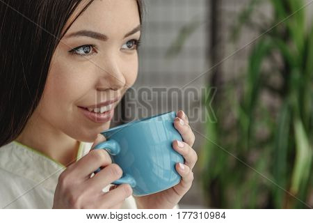 Portrait of asian woman drinking hot tasty beverage while looking away. Copy space