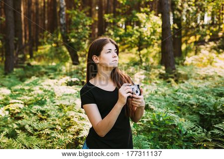 Happy Red-haired Caucasian Girl Young Woman Photographer Taking Pictures The Old Retro Vintage Film Camera In Summer Green Forest. Girl Dressed In A Black T-shirt