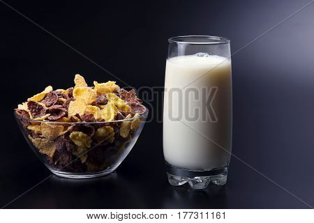 cornflakes in a plate and a glass of milk