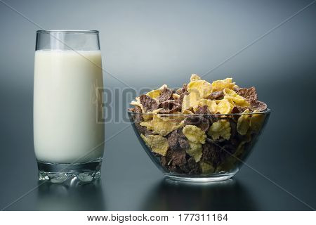 glass of milk and a plate of corn flakes