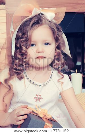 Beautiful, chubby little girl with long, blond, curly hair.Girl sitting near a Christmas tree with a gift in its hands.Creative toning of a photograph.