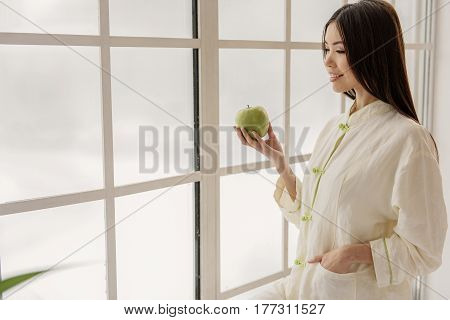 Attractive asian woman expressing dreaminess while holding green fruit. She looking away. Muse concept