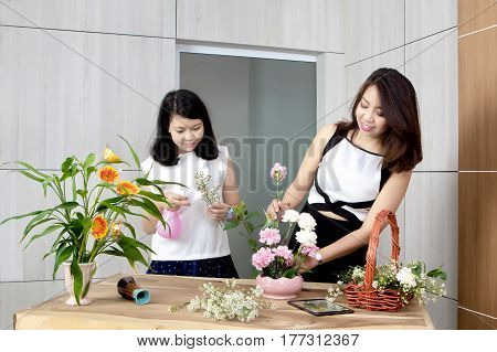 Young mother and teenage daughter putting beautiful flowers into a vase in concept of leisure activity within the family.