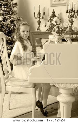 Beautiful, elegant little girl holding hands on the keys of a white Grand piano. Girl playing at the Christmas concert in the music school.Black-and-white photo. Retro style.